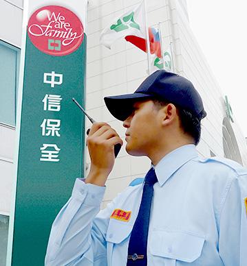 關於中信保全的介紹圖片,圖片中有一名保全拿著無線電站在中信保全招牌前