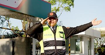 優質服務介紹一,駐衛保全服務,一名穿反光背心的保全人員站在停車場前指揮車輛